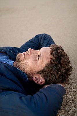 Mann liegt am Strand - p1124m1510948 von Willing-Holtz