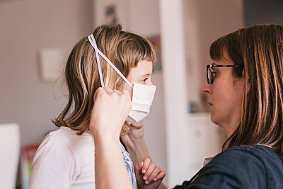 Mother putting medical mask on her daughter to protect himself from the coronavirus - p1166m2182919 by Cavan Images