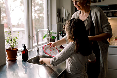 Daughter helping mother in kitchen at home - p426m2074447 by Maskot
