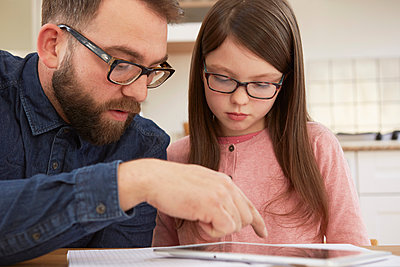 Mid adult man explaining homework to daughter at table - p429m1408156 by Emma Kim