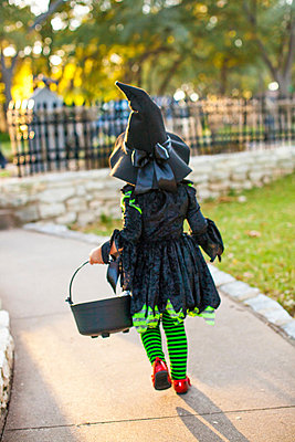 Back view of child in witch costume with bucket of treats - p429m819586 by Angela Bird