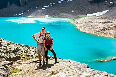 Female and Male hiker on rocky ridge with blue alpine lake in the background, Yoho National Park; Field, British Columbia, Canada - p442m2176989 by Michael Interisano