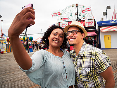 Couple posing for selfie on boardwalk at amusement park - p555m1304531 by Granger Wootz