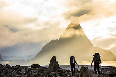 Rear view of backpackers approaching dramatic mountain, Mt. Loki - p1166m2189676 by Cavan Images