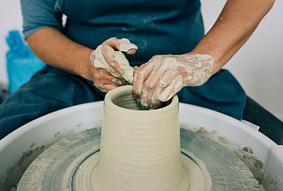 woman moulding clay on a pottery wheel making a vase - p1166m2285740 by Cavan Images