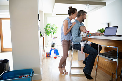 Parents with baby using laptop in kitchen - p1192m2088298 by Hero Images