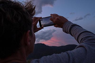 Tourist photographing evening sky - p1532m2090268 by estelle poulalion