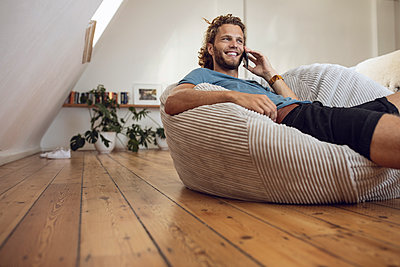Smiling young man relaxing in beanbag at home talking on the phone - p300m2156501 by Maya Claussen
