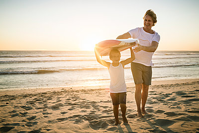 Happy father and son with surfboard walking on the beach at sunset - p300m2167513 by Floco Images