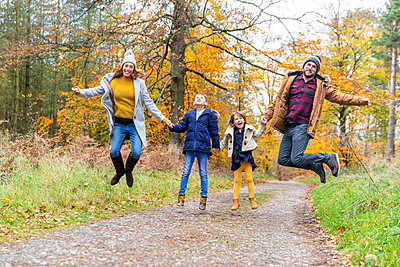 Family holding hands while jumping on forest path during autumn - p300m2256777 by William Perugini