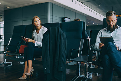 Thoughtful young businesswoman looking away while sitting with colleague in airport departure area - p426m2074729 by Maskot