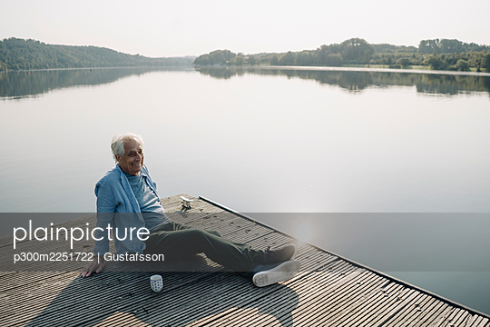 Smiling man looking away while relaxing on pier - p300m2251722 by Gustafsson