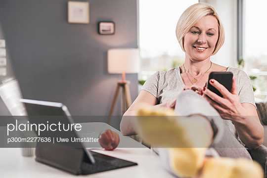 Smiling woman using smart phone while leaning legs on table at home - p300m2277636 by Uwe Umstätter