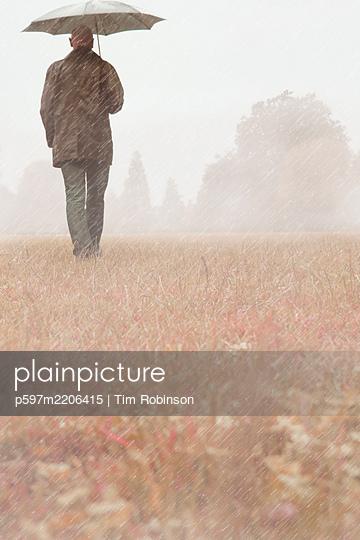 Man walking through park in the rain carrying umbrella - p597m2206415 by Tim Robinson