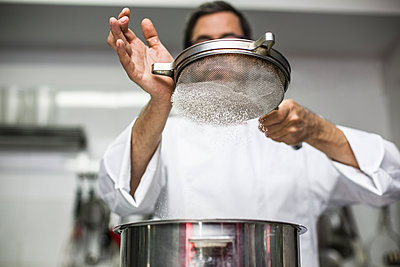 Chef sifting flour into bowl - p1166m2130227 by Cavan Images