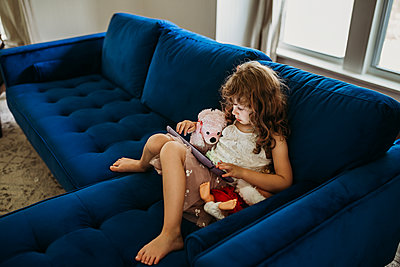 Young girl sitting inside on blue couch using tablet - p1166m2201670 by Cavan Images