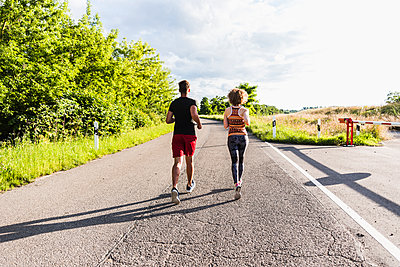 Young couple running on country road - p300m1157365 by Uwe Umstätter