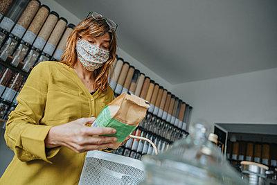 Woman shopping in zero waste shop, Cologne, NRW, Germany - p300m2256188 von Mareen Fischinger