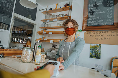 Mobile payment being made in zero waste shop, Cologne, NRW, Germany - p300m2256191 von Mareen Fischinger