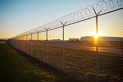 Sunset through a chain linked fence. - p343m1101613f by Christopher Kimmel
