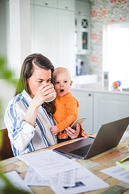 Working businesswoman drinking coffee while carrying yawning daughter in dining room - p426m2117028 by Maskot