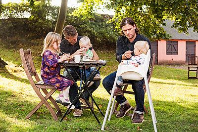 Full length of men feeding children in park - p426m977528f by Astrakan