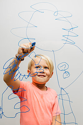 Boy drawing with marker pen onto glass wall - p429m1504959 by JFCreatives