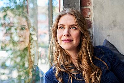Frau sitzt am Fenster, Porträt - p890m1440032 von Mielek