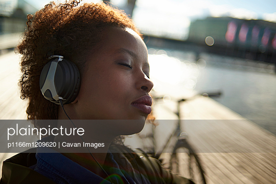 Close-up of relaxed woman with eyes closed listening music
