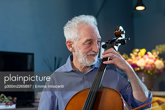 Smiling senior man playing cello at home - p300m2265897 by Emma Innocenti