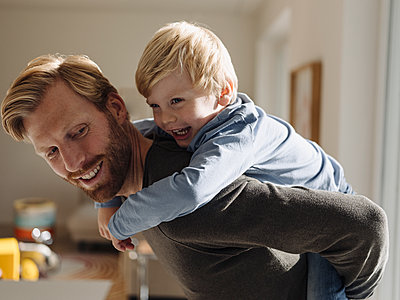 Happy father carrying son piggyback at home - p300m2166586 by Kniel Synnatzschke