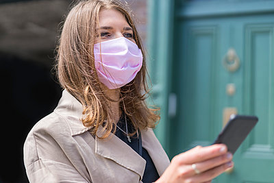 Young woman using smart phone while wearing protective face mask standing during covid-19 - p300m2220544 by Boy photography