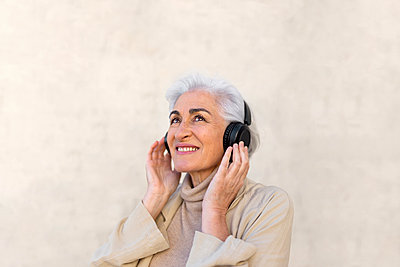 Smiling woman day dreaming while wearing headphones in front of wall - p300m2281467 by PICUA ESTUDIO