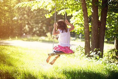 Girl playing on swing in field - p555m1409497 by Shestock