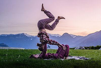Two young women practicing acroyoga on grass in front of mountain range at sunset, Squamish, British Columbia, Canada - p924m2039615 by Alex Eggermont