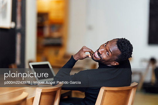 Smiling businessman resting while sitting on chair at cafe - p300m2243978 by Miguel Angel Partido Garcia