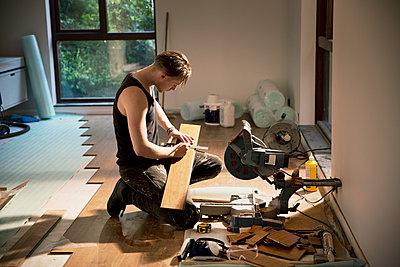 Construction worker preparing hardwood flooring in house - p1023m2046698 by Tom Merton