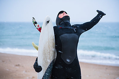 Young woman going winter surfing in snow - p1166m2177048 by Cavan Images