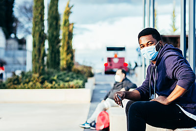 Portrait of an African American boy with face mask sitting on a bench in an urban space. - p1166m2254937 by Cavan Images
