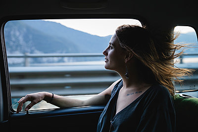 Young woman sitting on backseat in a car looking out of window - p300m2042858 by Michela Ravasio