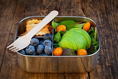 Lunch box of leaf salad, avocado, blueberries, tomatoes and crackers - p300m2080875 von Larissa Veronesi