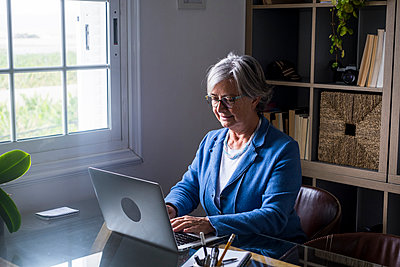 Smiling elderly female entrepreneur working on laptop while sitting at home - p300m2276587 by Simona Pilolla