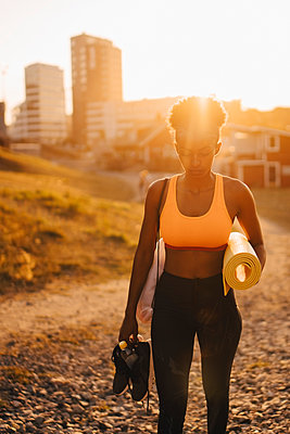Young female athlete with sports shoe and exercise mat standing on land during sunset - p426m2270767 by Maskot