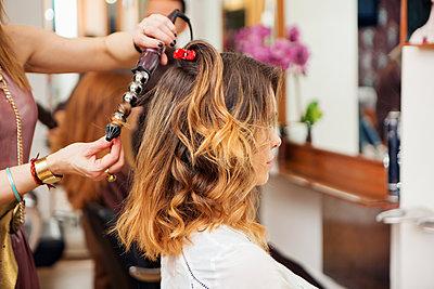 Hairdresser using curling tongs on customer's long brown hair in salon - p429m1408237 by Nancy Honey