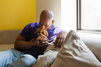 Mid adult male sitting on sofa with dog - p924m805965f by Zave Smith