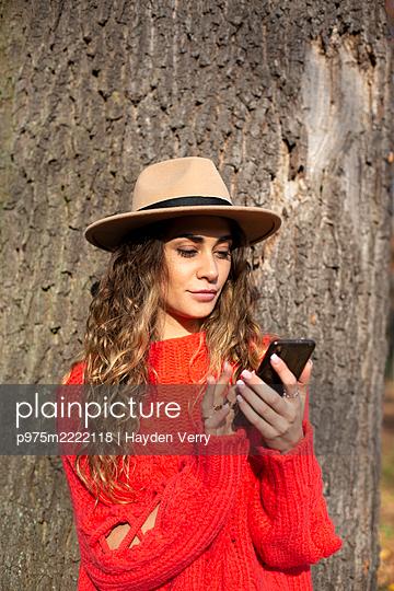 Junge Frau im roten Pullover verschickt eine SMS - p975m2222118 von Hayden Verry