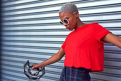 Cool young woman playing tambourine outside garage - p1023m2190269 by Trevor Adeline