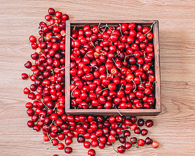 Overhead view of cherries in crate on wooden table - p1166m2024799 by Cavan Images