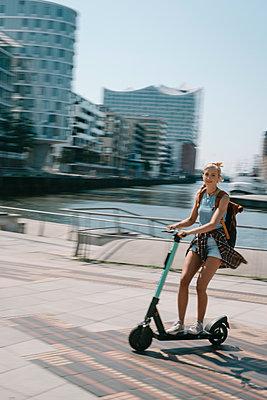 Junge Frau unterwegs mit dem E-Scooter - p299m2108618 von Silke Heyer