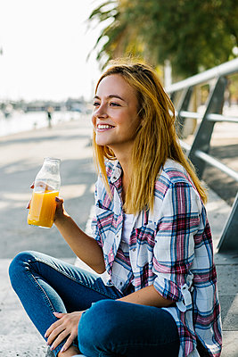 Young woman looking away while drinking juice sitting on footpath in city - p300m2226694 by Xavier Lorenzo
